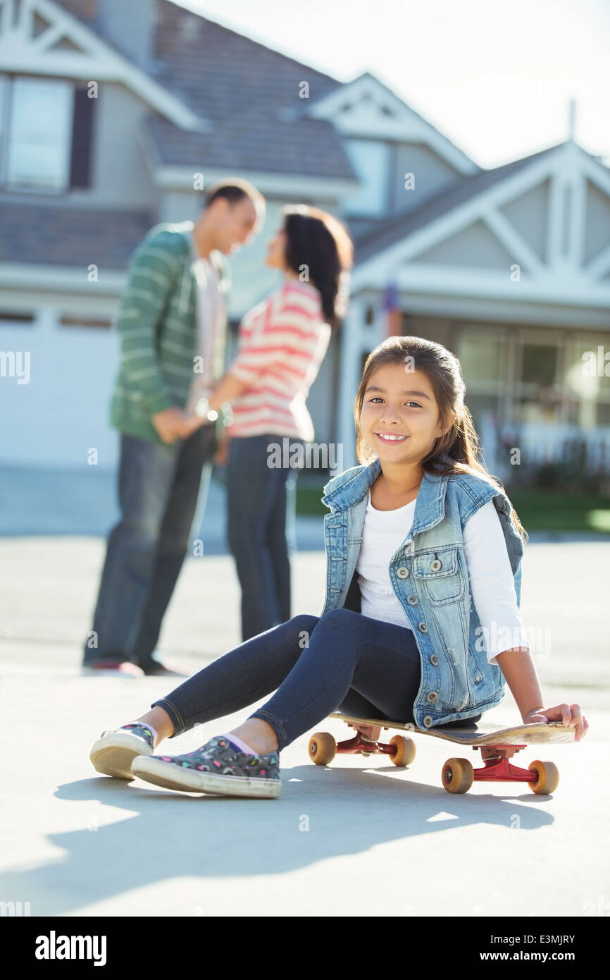 Portrait of smiling girl on skateboard in driveway Stock Photo