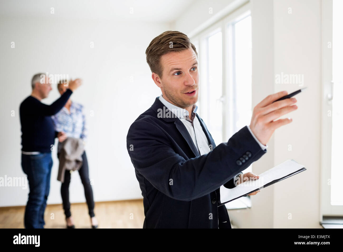 Real estate agent examining house with couple discussing in background - Stock Image