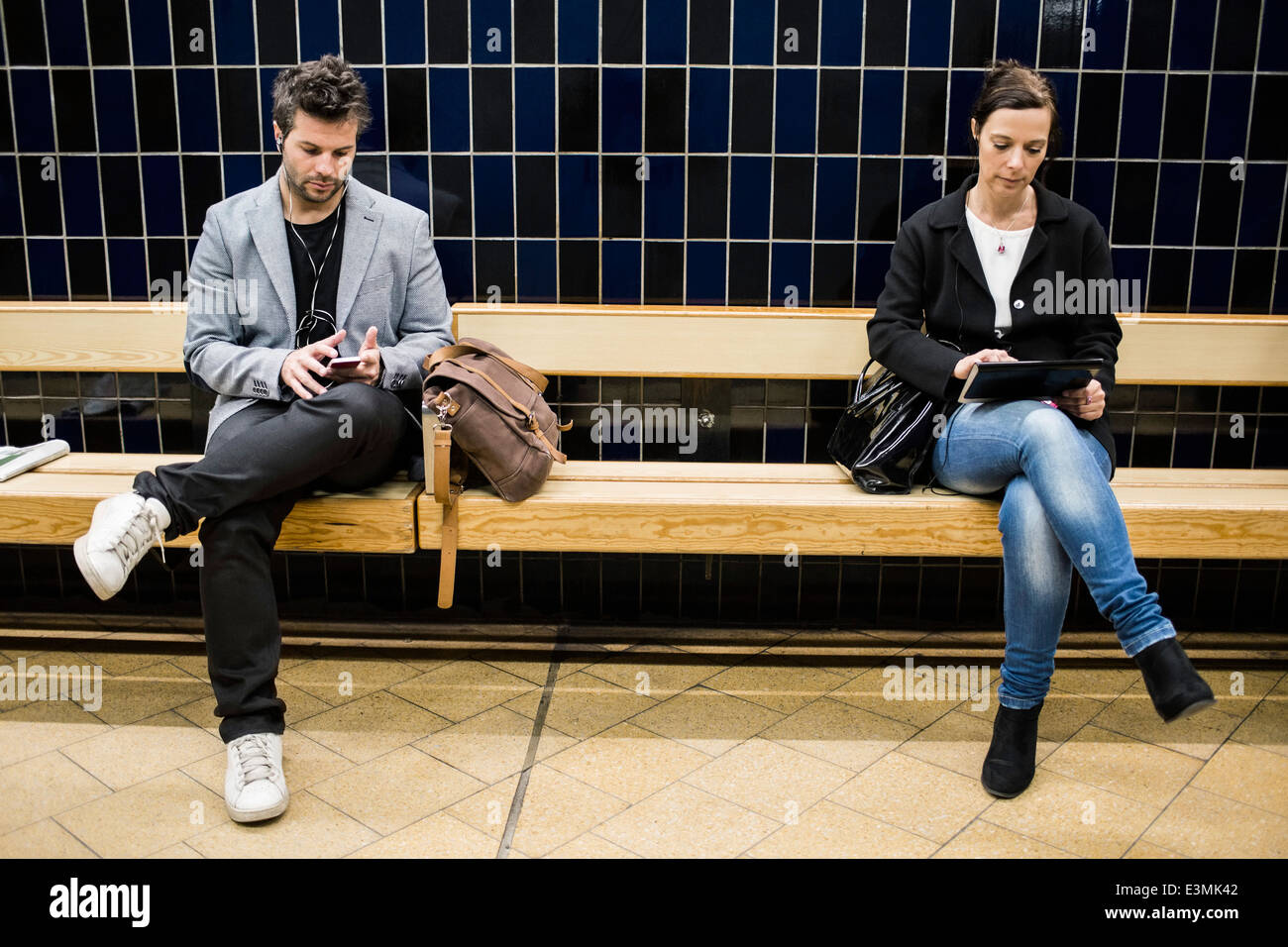 Full length of people using technologies on bench at subway station - Stock Image