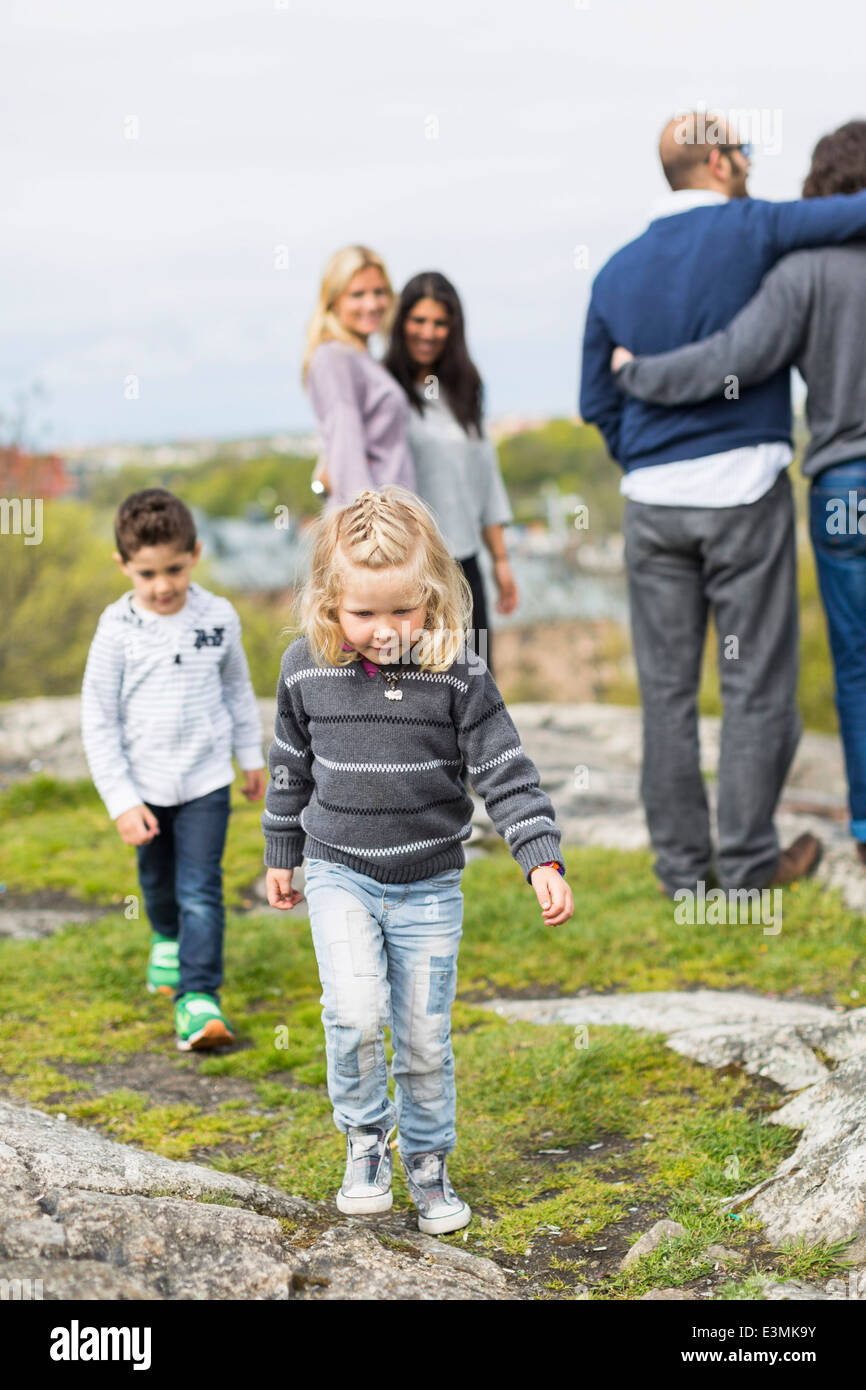 Children walking on rock with homosexual couple in background - Stock Image
