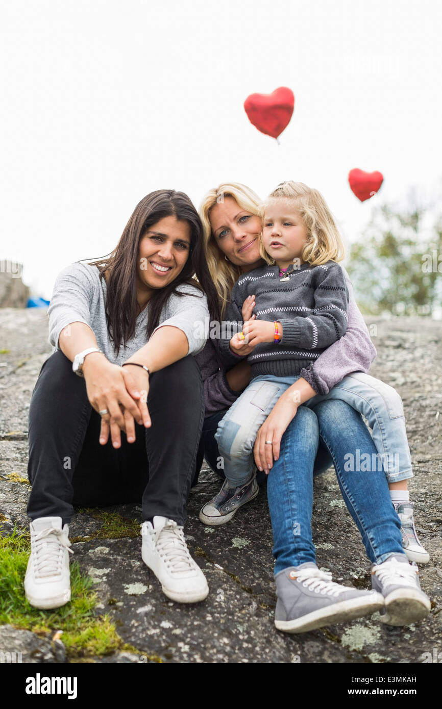 Portrait of happy female homosexual family relaxing on rock - Stock Image