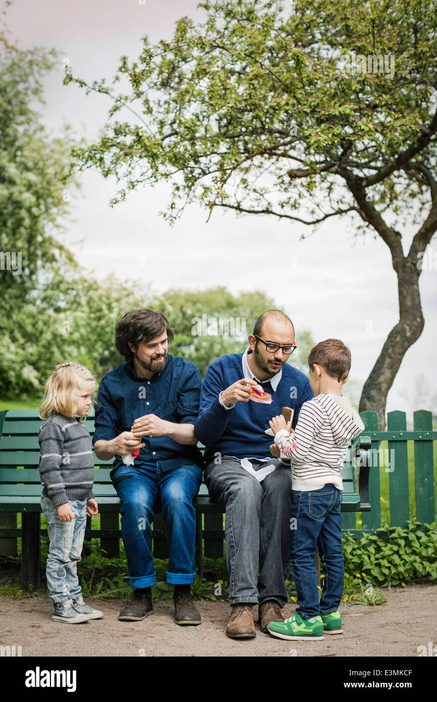 Full length of male homosexual family spending leisure time at park - Stock Image
