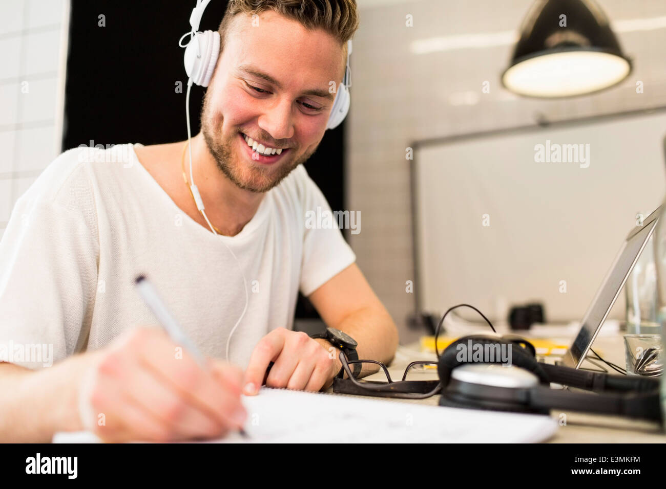 Happy young businessman wearing headphones while writing in book at creative office - Stock Image