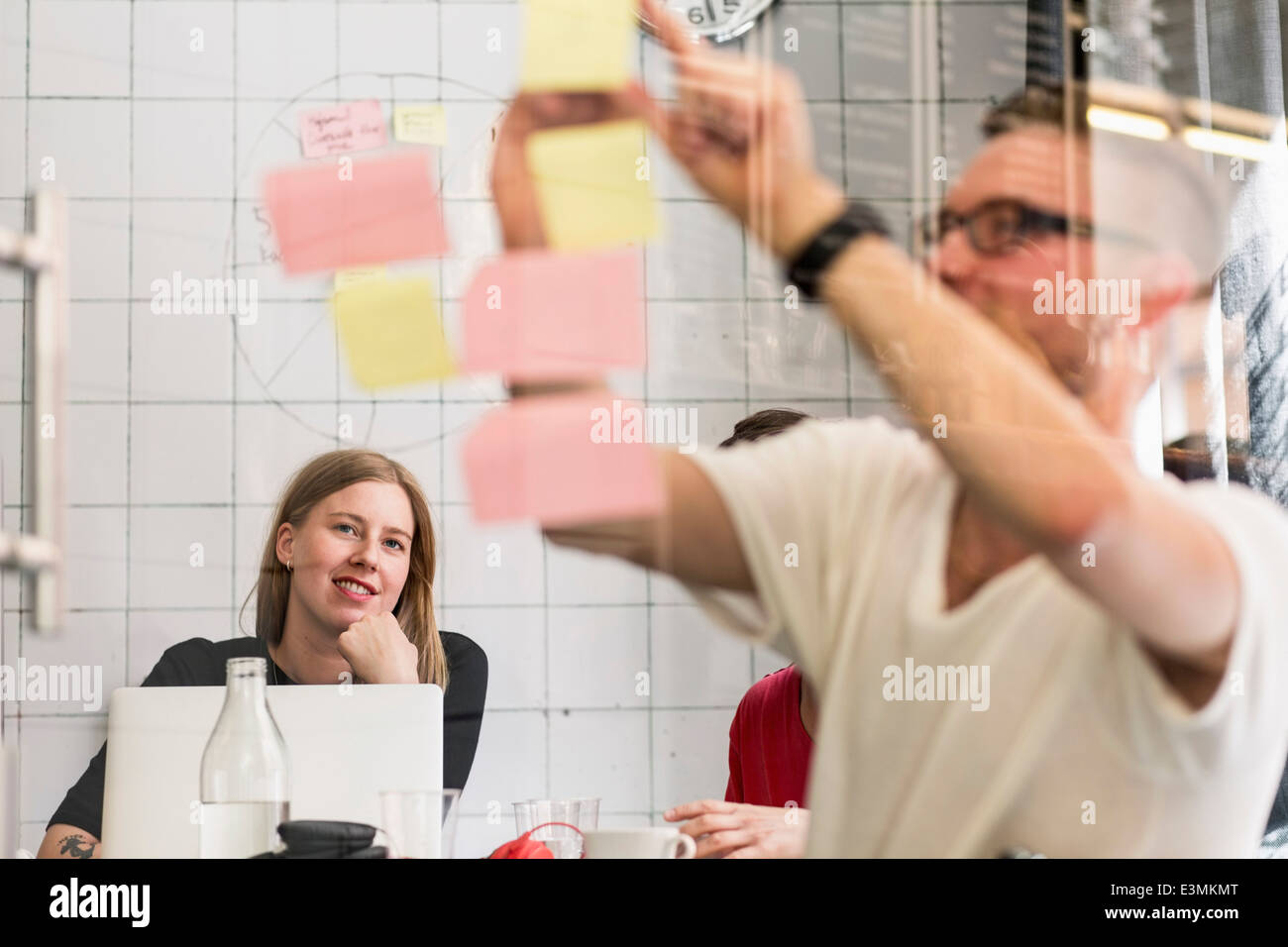 Young businessman writing ideas on adhesive notes with colleagues in background at creative office - Stock Image