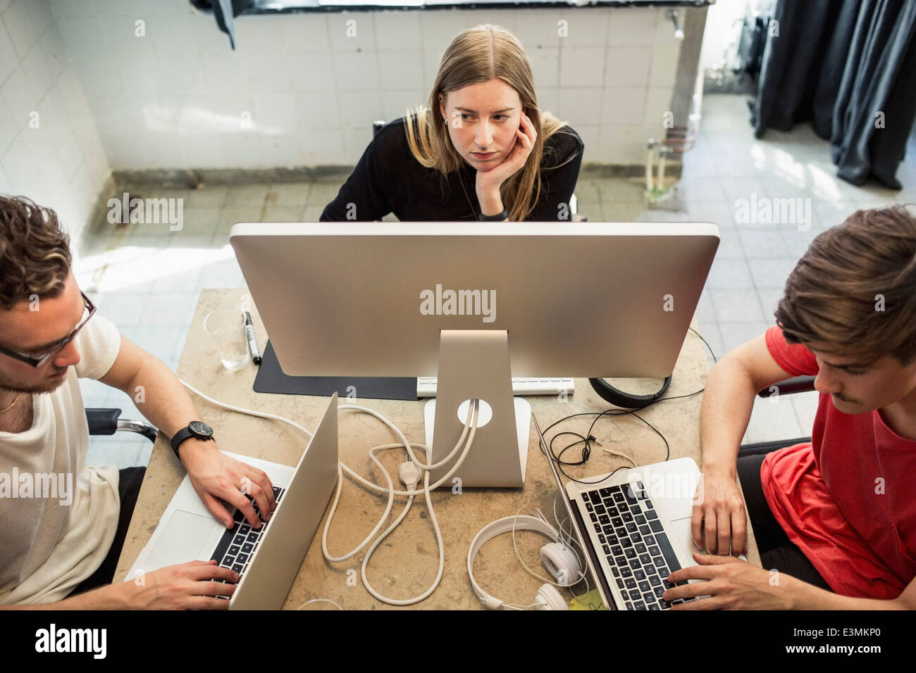 High angle view of young business people using technologies in creative office - Stock Image