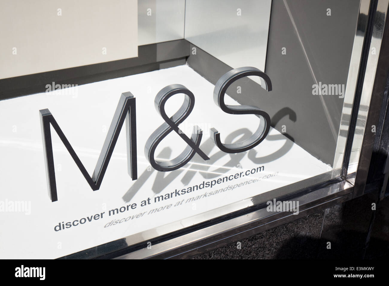 Bright sunshine on the Marks & Spencer company logo on a glass store front casting a shadow in the shop windows - Stock Image