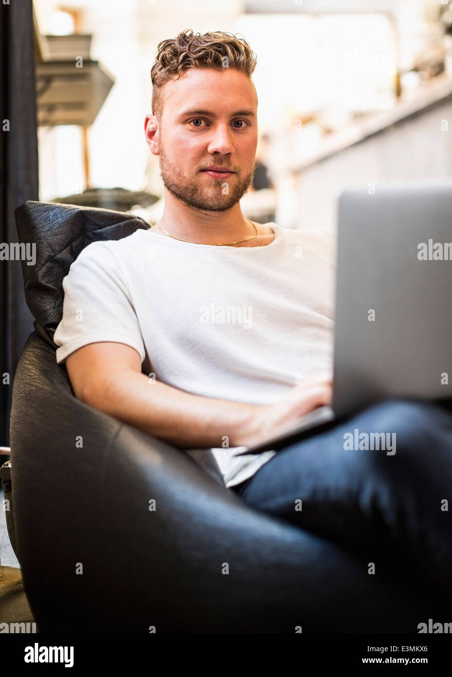 Portrait of confident young businessman using laptop while sitting on bean bag chair in new office - Stock Image
