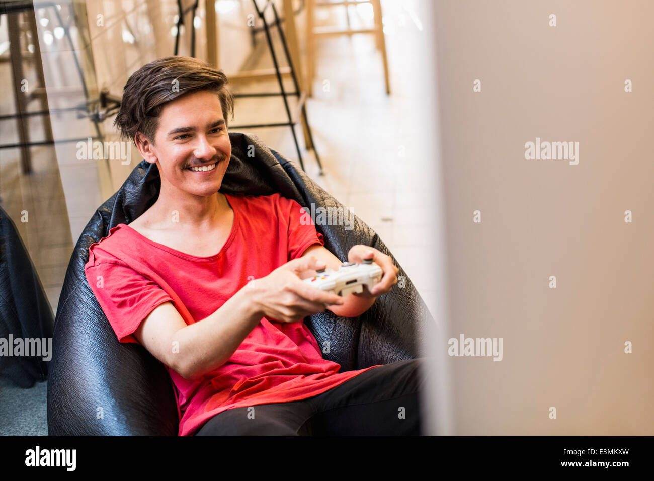 Happy young man playing video game while sitting on bean bag at home - Stock Image