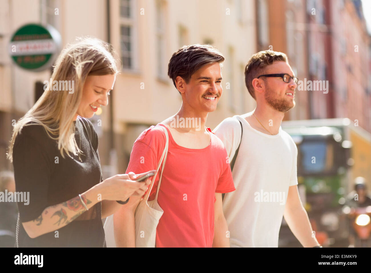 Happy young friends walking on city street - Stock Image