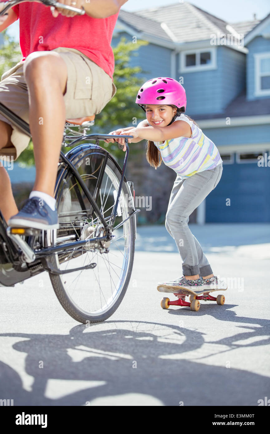 Daughter on skateboard pushing father on bicycle - Stock Image