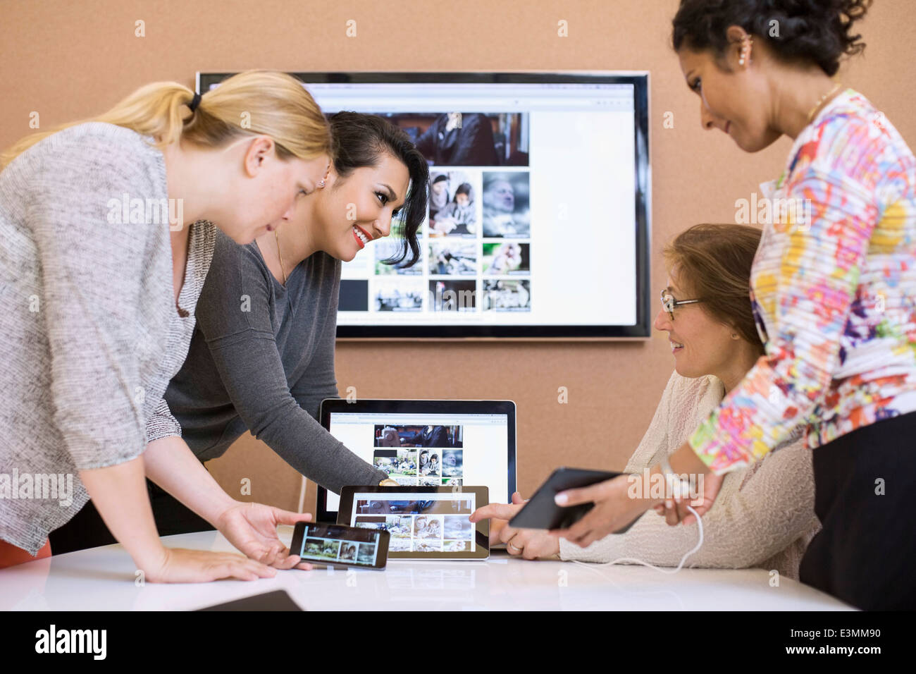 Female photo editors using various technologies in creative office - Stock Image