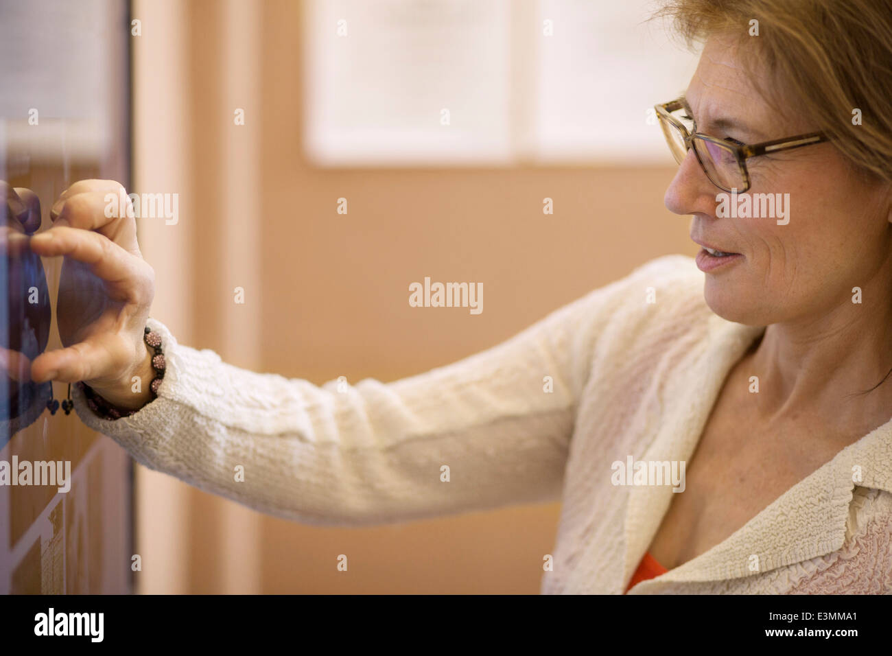 Photo editor analyzing photographs on television in creative office - Stock Image