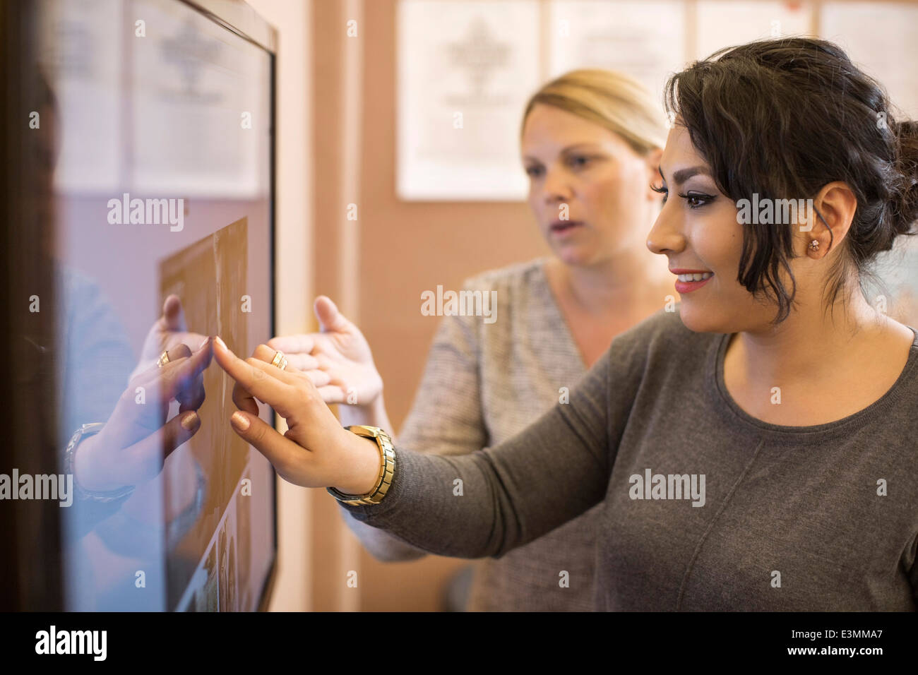 Photo editors analyzing photographs on television in creative office - Stock Image