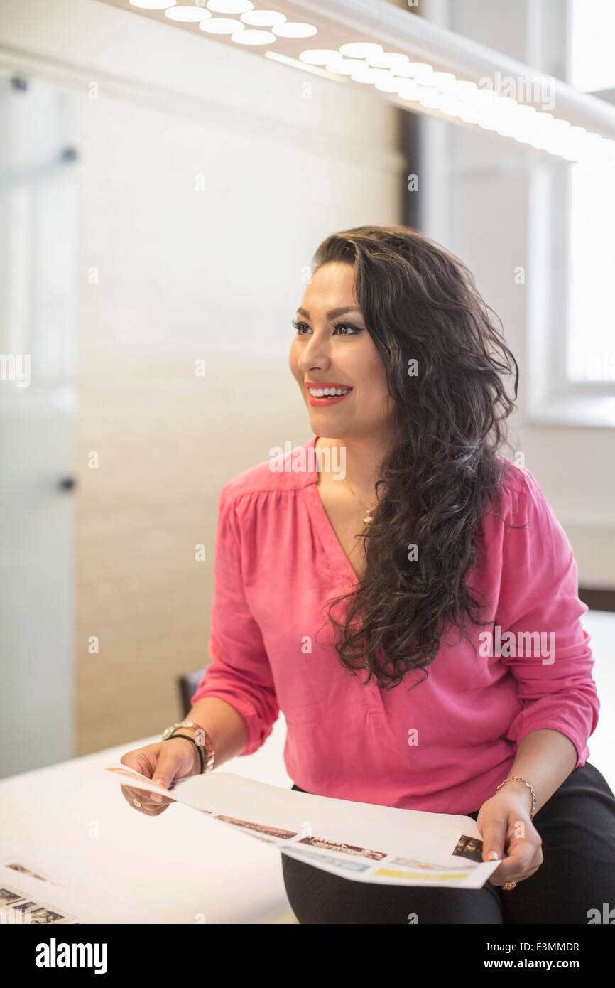 Smiling photo editor holding document in creative office - Stock Image