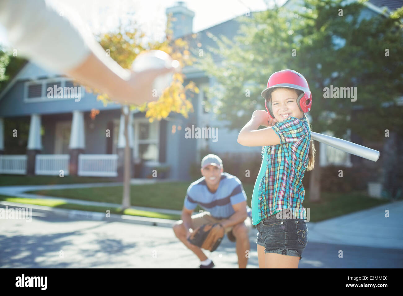 Family playing baseball in street - Stock Image