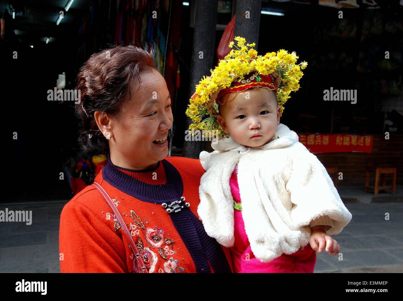 HUANG LONG XI, CHINA: GRANDMA WITH HER GRANDSON WHO WEARS A TRADITIONAL  FLORAL WREATH HAT - Stock Image