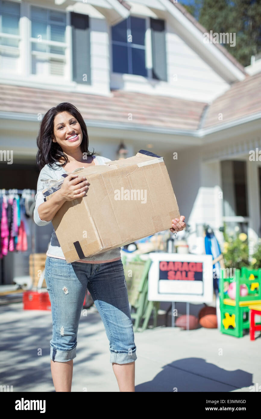 Portrait of smiling woman with box at garage sale - Stock Image
