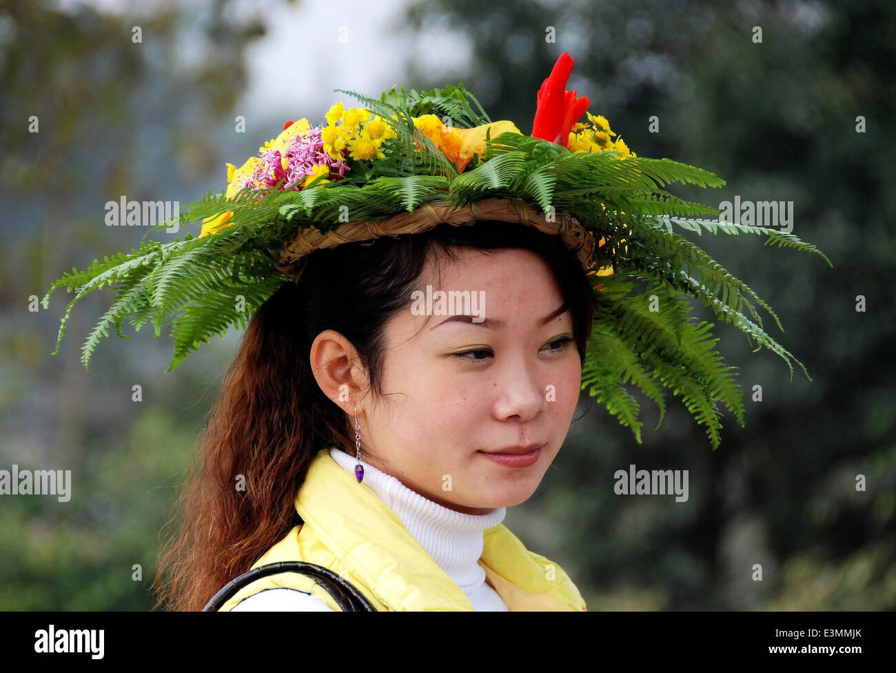 Huang Long Xi, China: Young Woman wearing a floral wreath hat - Stock Image