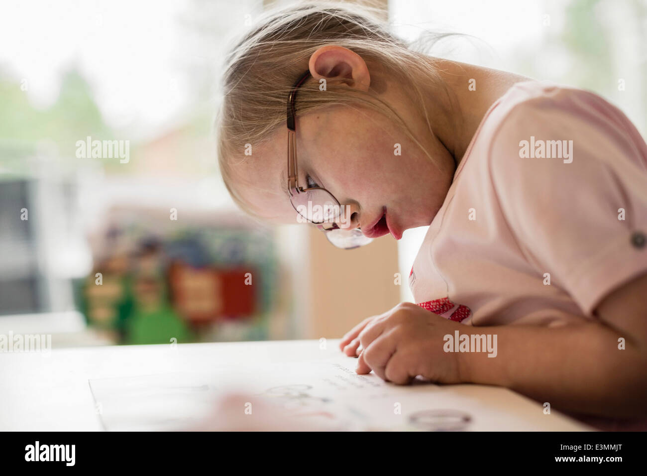 Girl with down syndrome studying at table - Stock Image
