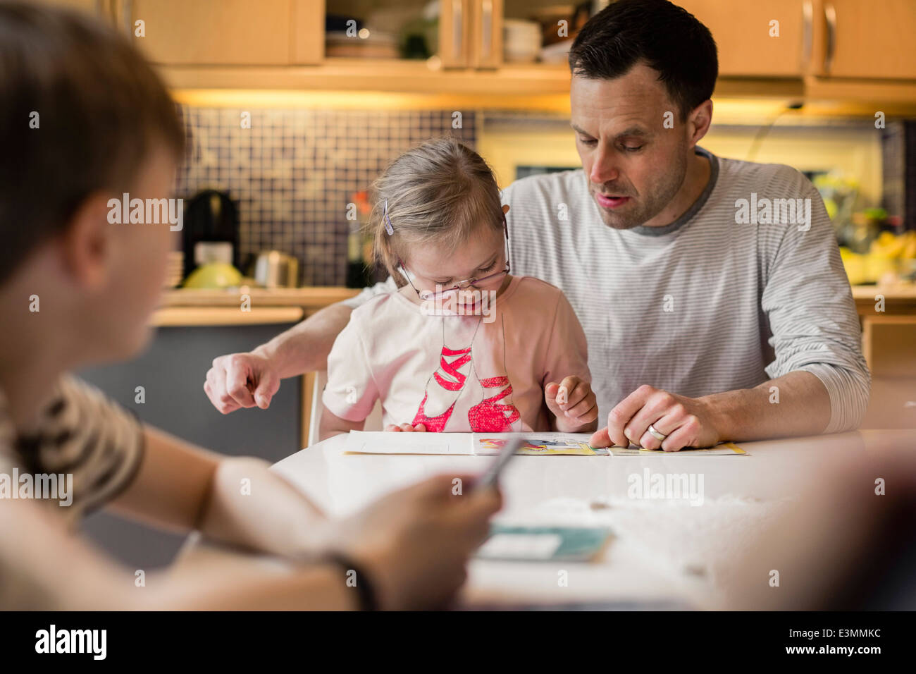Father teaching daughter with son in foreground at home - Stock Image