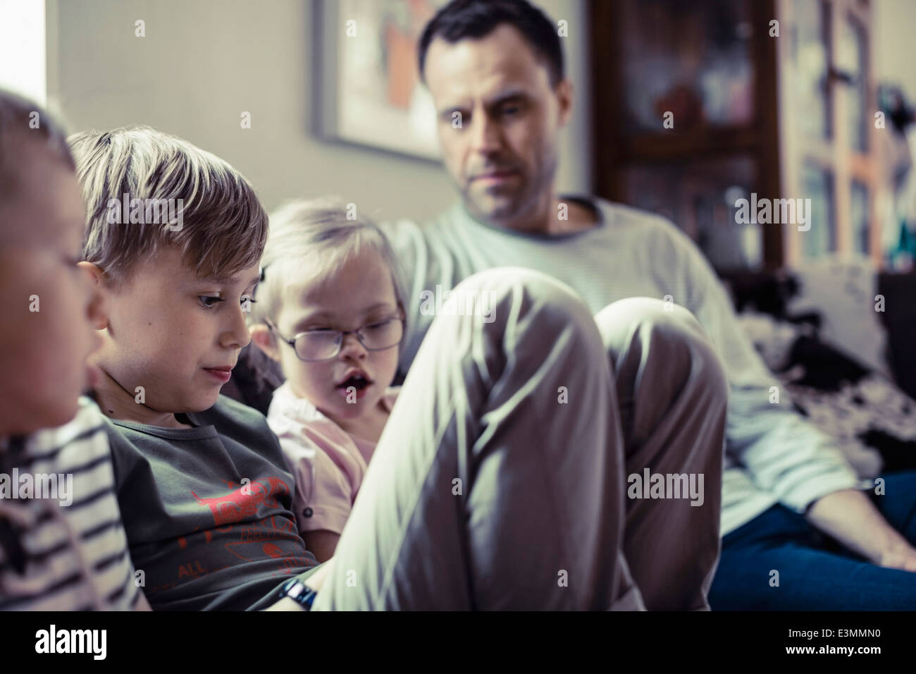 Siblings sitting with father in house Stock Photo