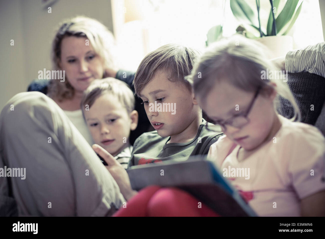 Siblings sitting with mother in house - Stock Image