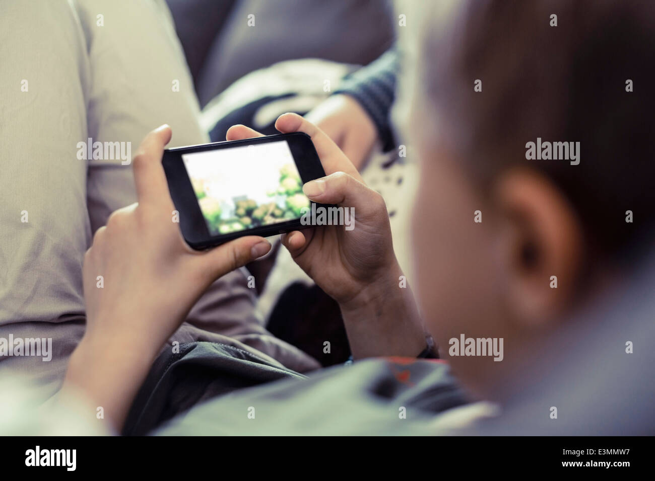 Boy playing game on mobile phone at home - Stock Image