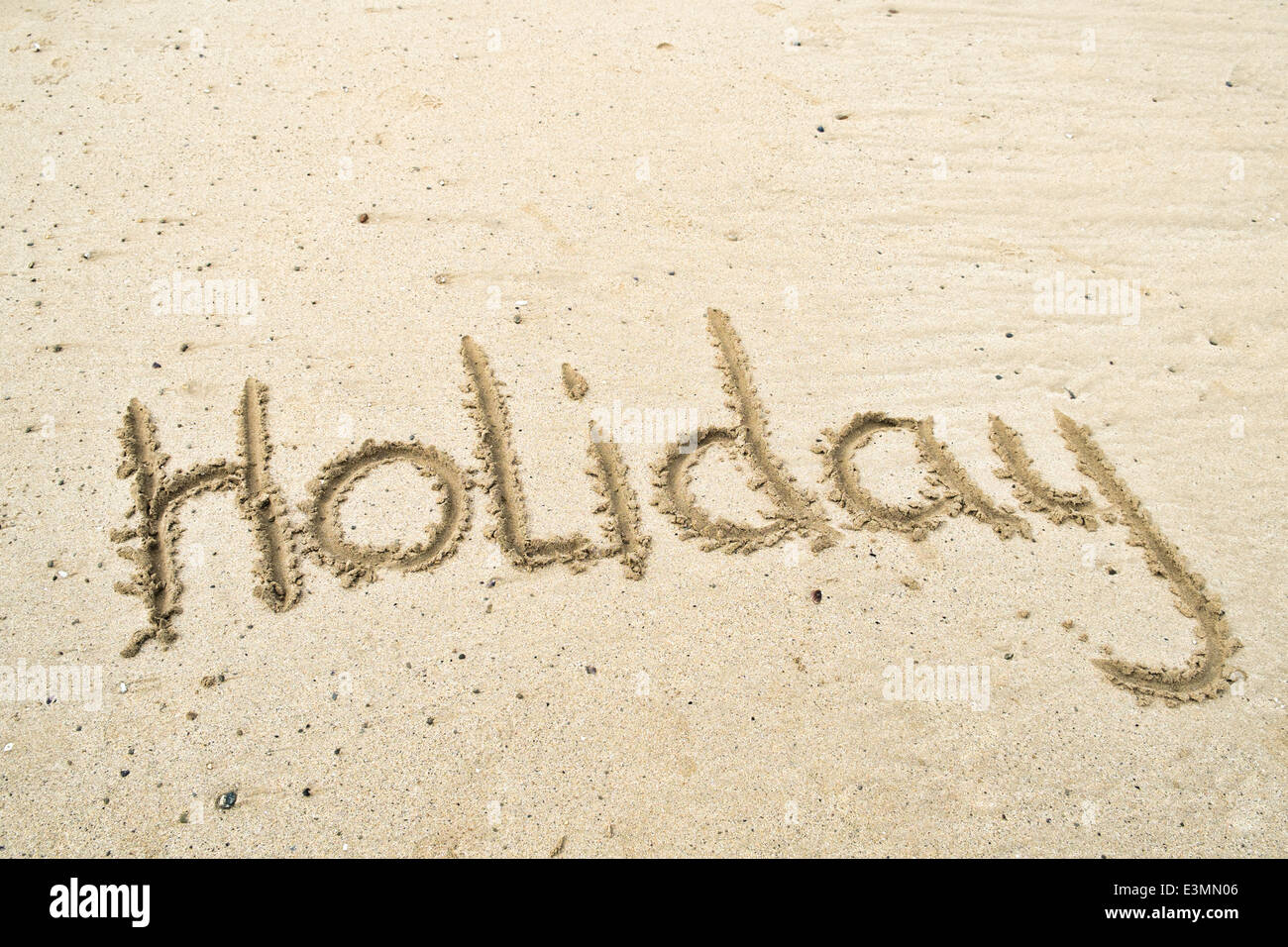 The Word holiday written in sand on a beach - Stock Image