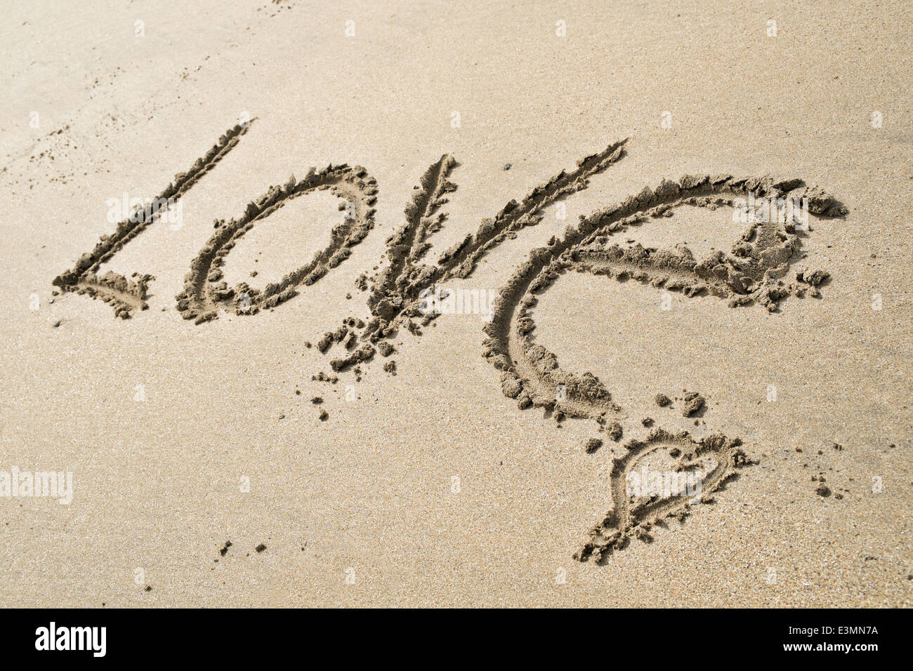The word Love written in the sand on a sunny, sandy beach - Stock Image