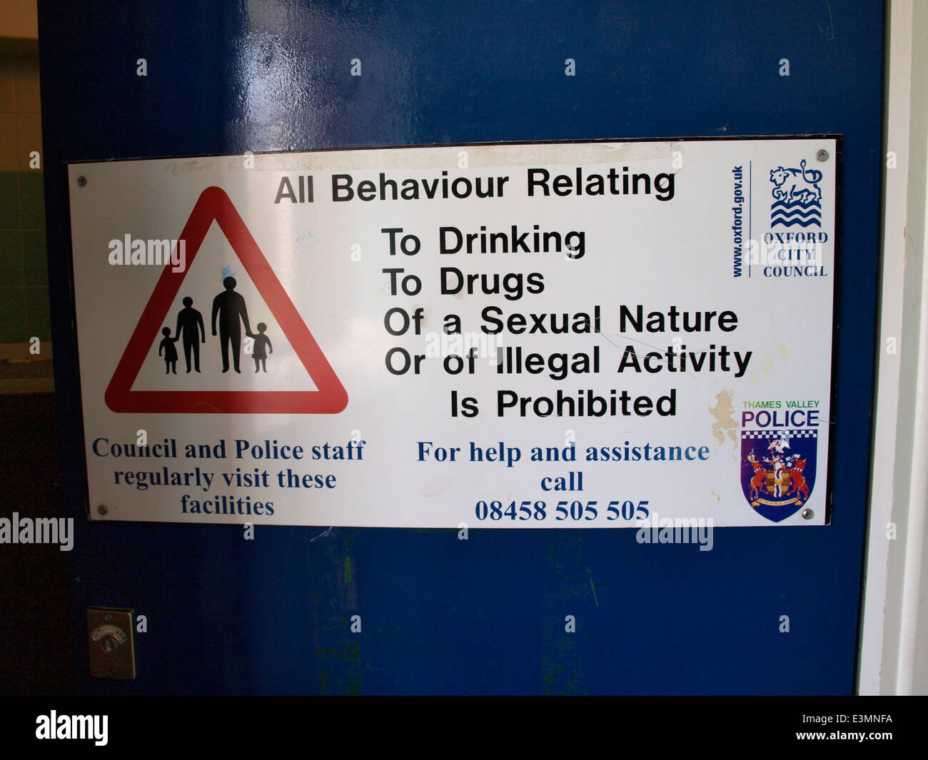 Oxford City Council and Thames Valley Police sign on a public toilet door, Oxford, UK - Stock Image