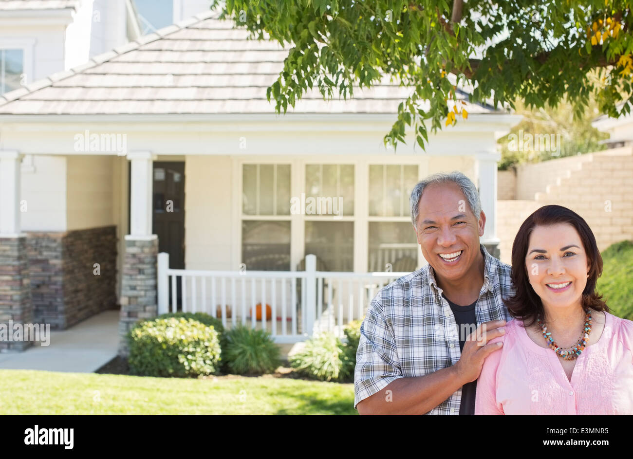 Portrait of smiling couple outside house - Stock Image