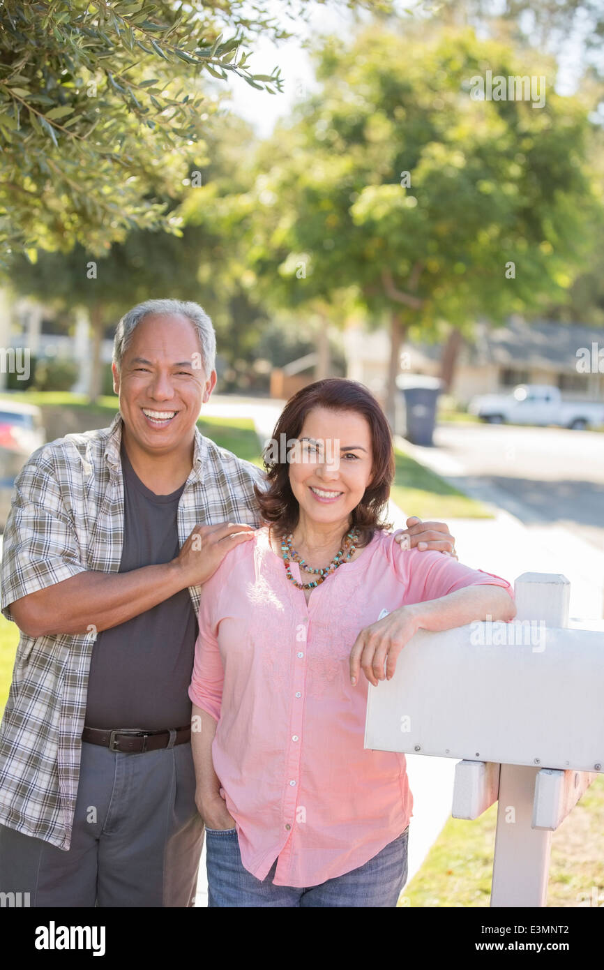 Portrait of smiling couple at mailbox - Stock Image