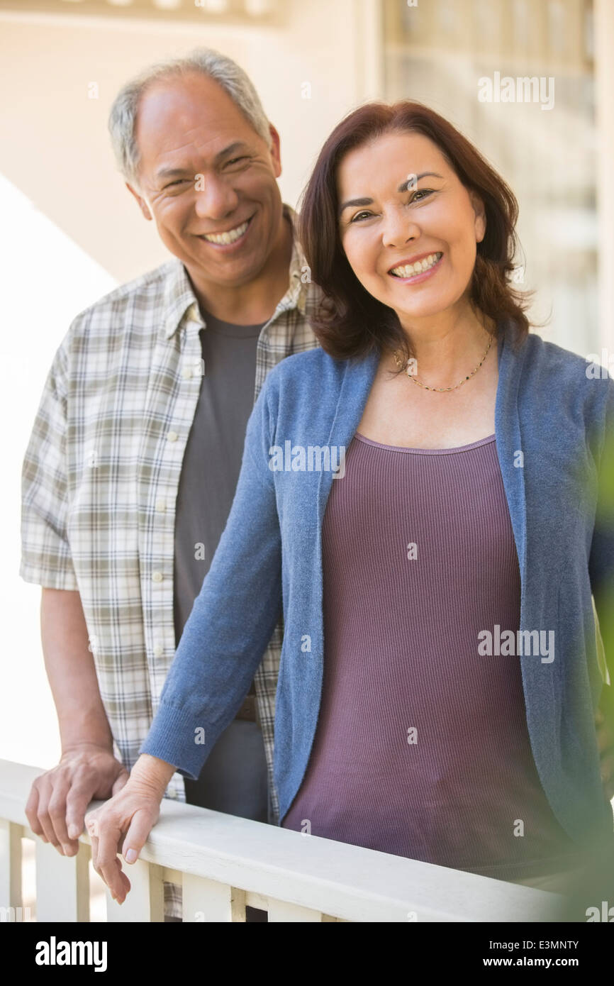 Portrait of smiling couple on porch - Stock Image