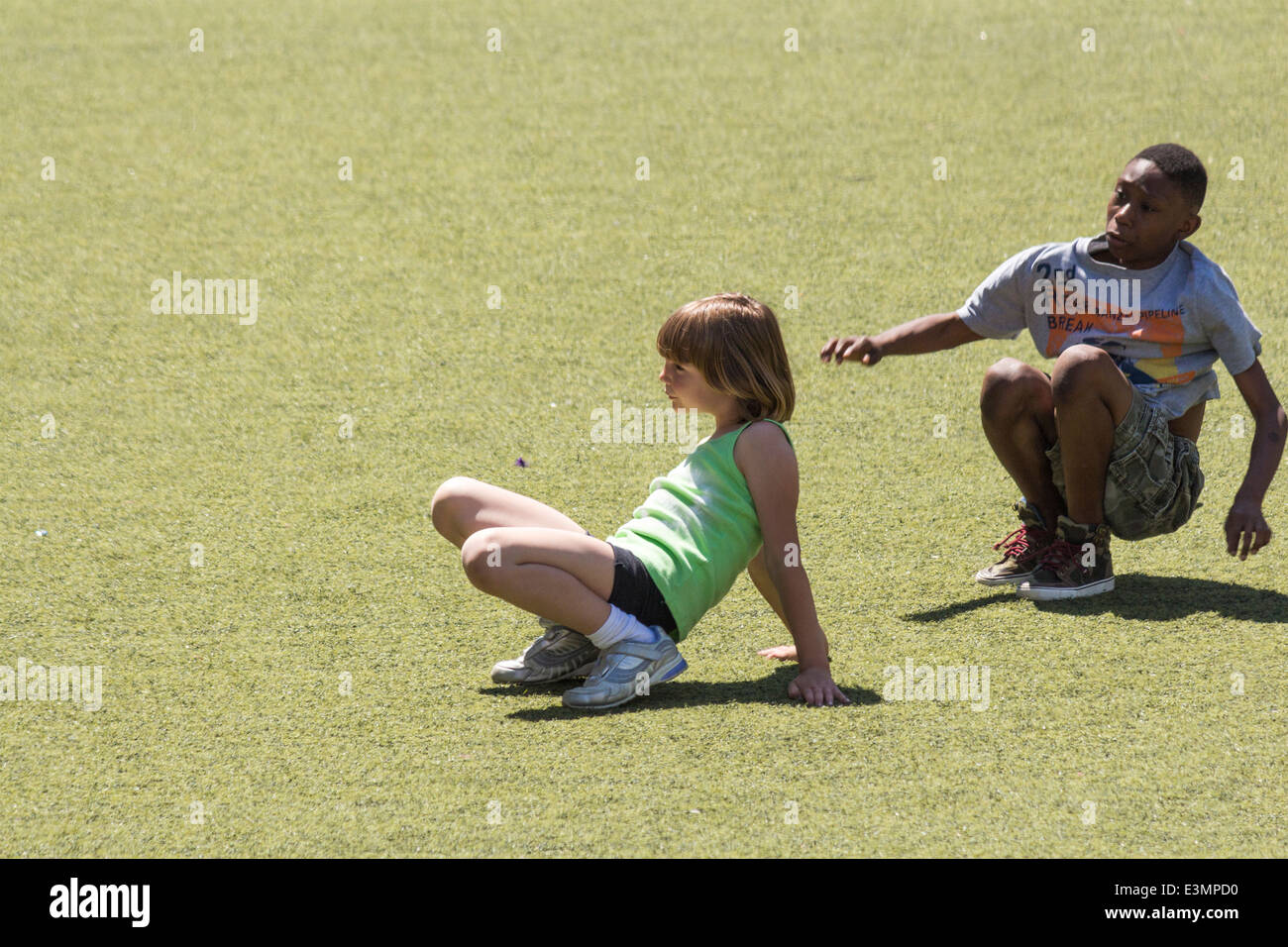 Young pre-teen girl and boy playing on the grass at Harbourfront in Toronto Ontario - Stock Image