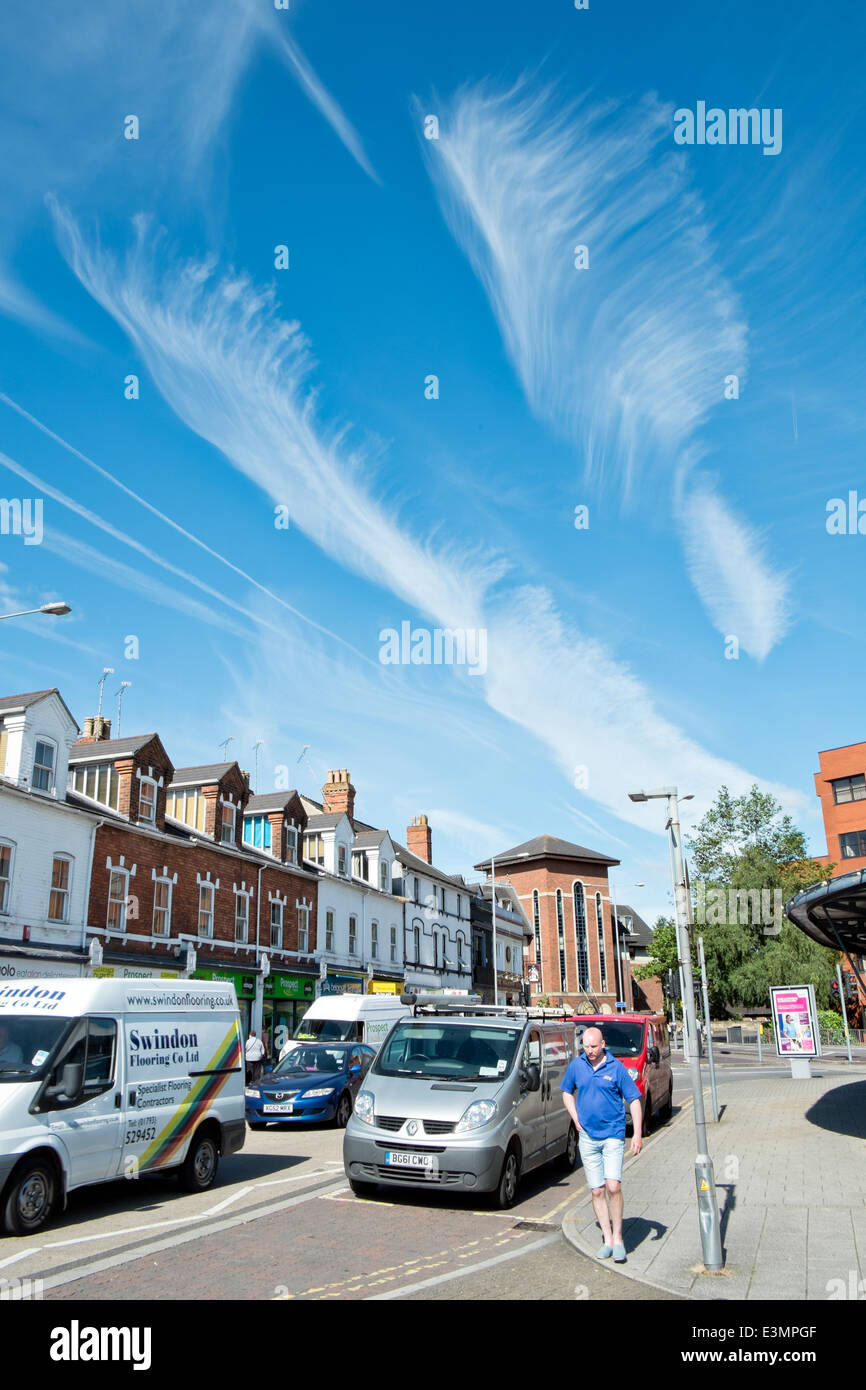 Feather like cirrus cloud formations in an azure summer sky above a typical British street scene - Stock Image