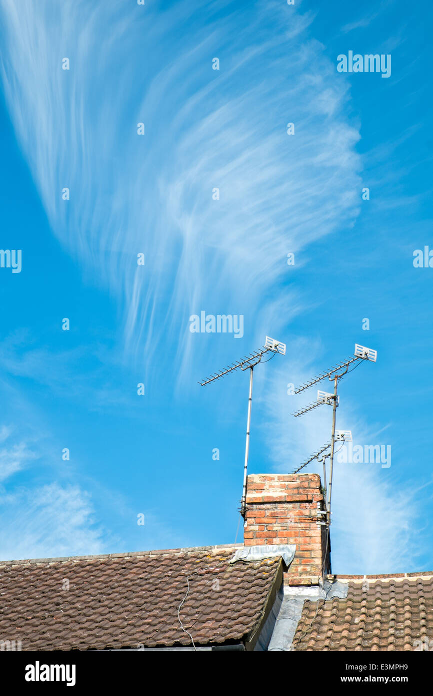 A feather like cirrus cloud formation above a rooftop & chimney with aerials against an azure summer sky - Stock Image