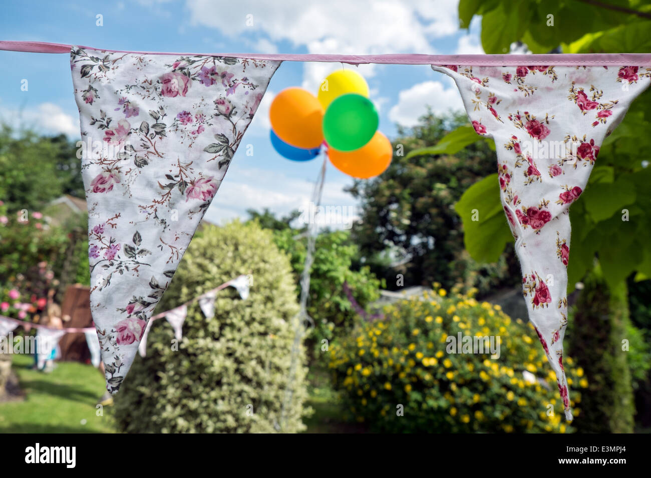 Shabby chic vintage bunting with defocused, colorful balloons on a sunny day at a garden party. - Stock Image