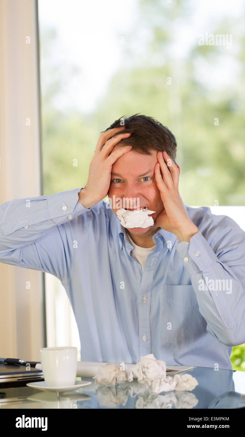 mature man showing stress by biting wad of paper while working from home with bright daylight coming in from window - Stock Image