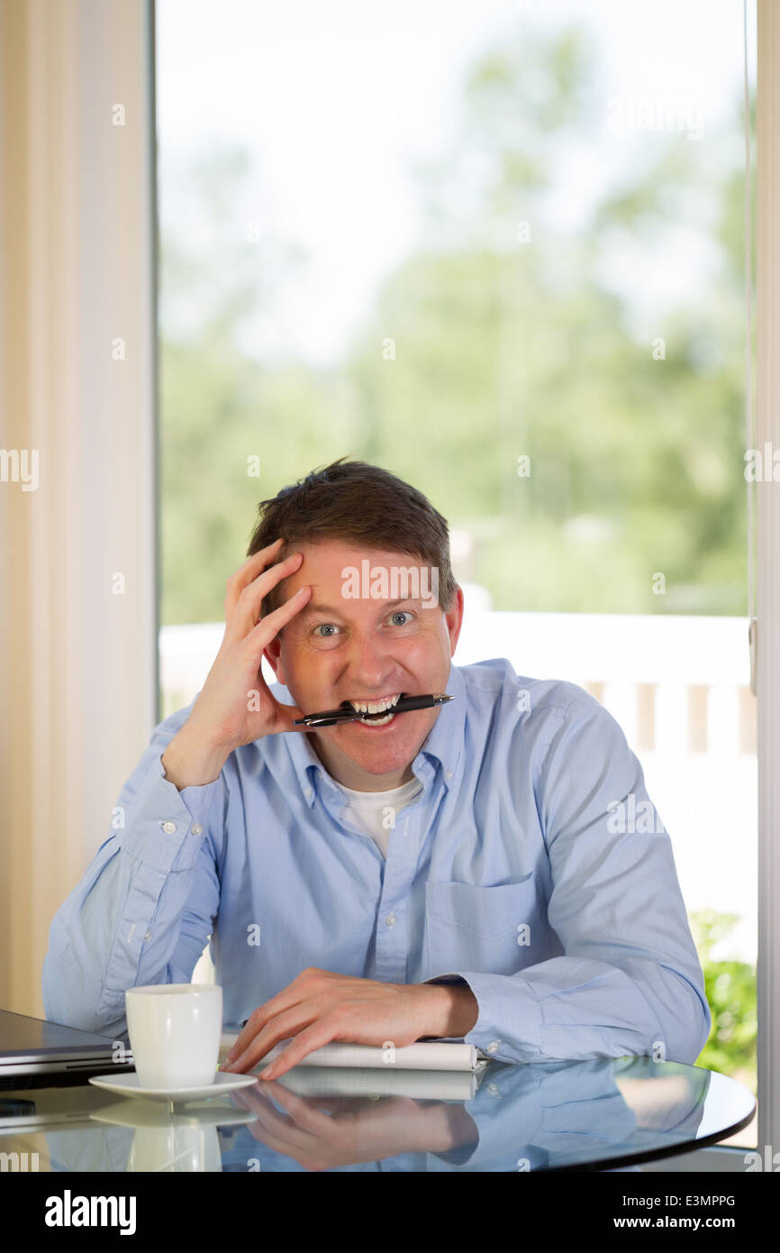 mature man showing extreme stress, looking forward, while working from home with bright daylight coming in from - Stock Image