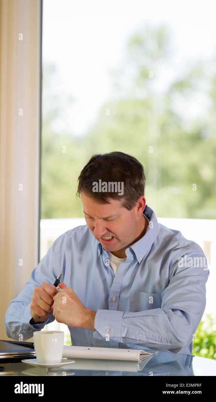 mature man showing stress by crumbling paper while working from home with bright daylight coming in from window - Stock Image