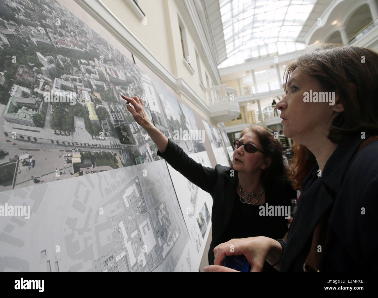 ITAR-TASS: MOSCOW, RUSSIA. JUNE 25, 2014. Women look at a project, winner of the close competition for the architectural Stock Photo
