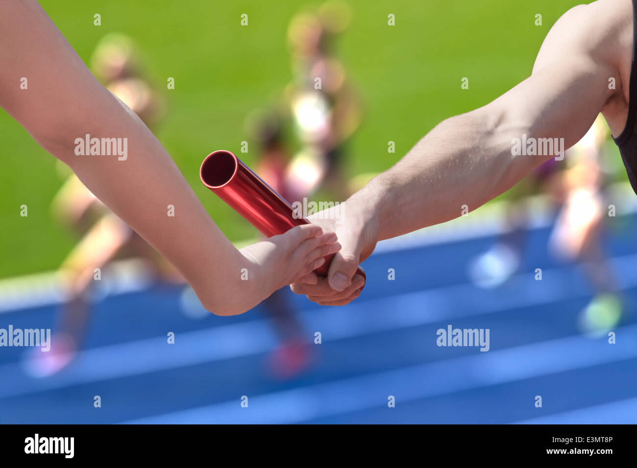 Male relay runner hands over the red baton to female runner - Stock Image