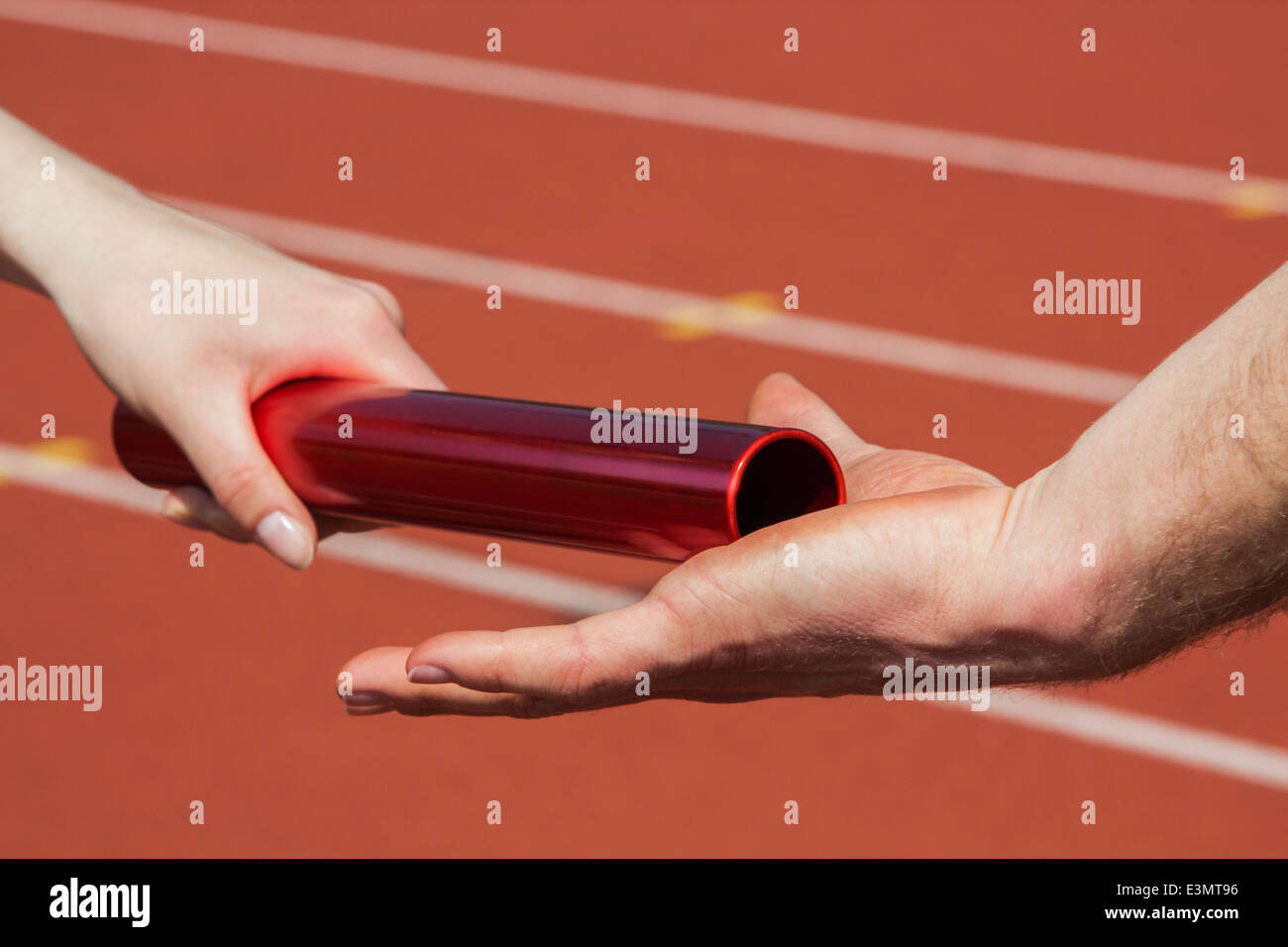 Female athlete hands over the relay race bar to a male athlete - Stock Image