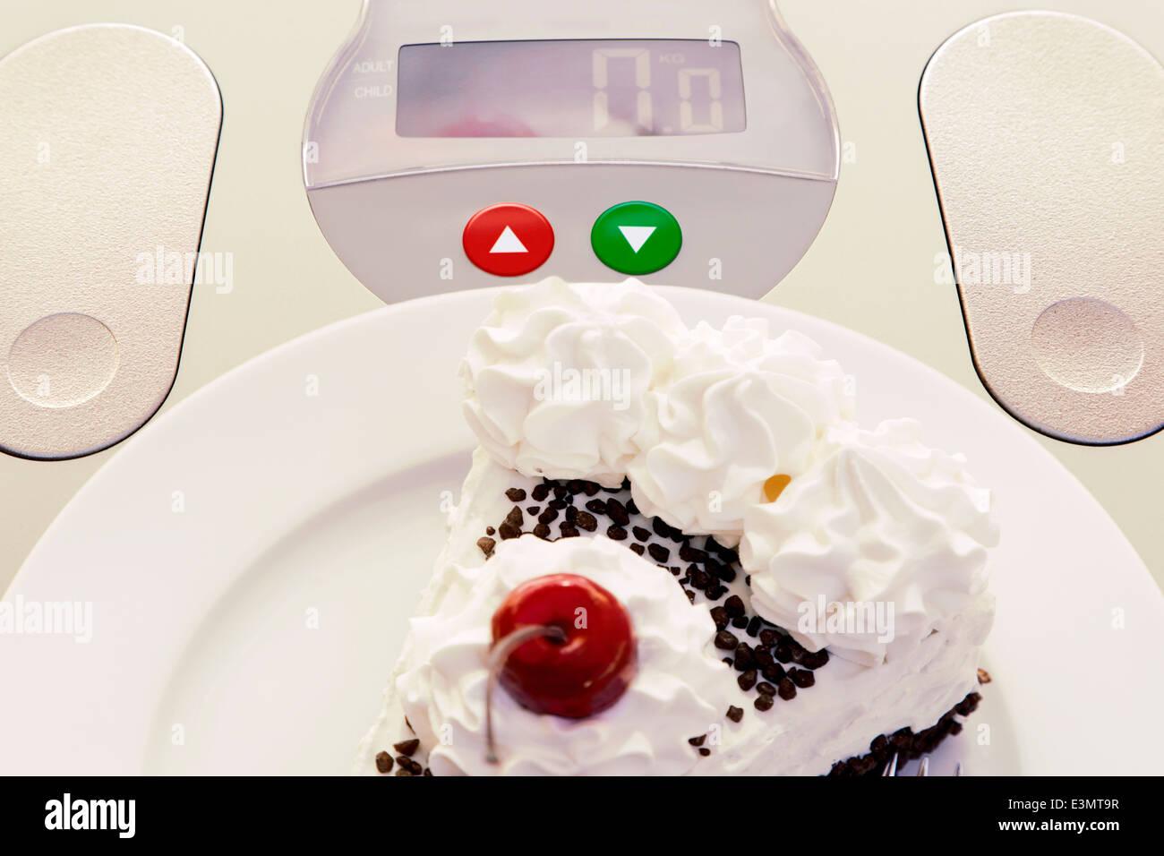 Cake on bathroom scale symbolizes overweight - Stock Image