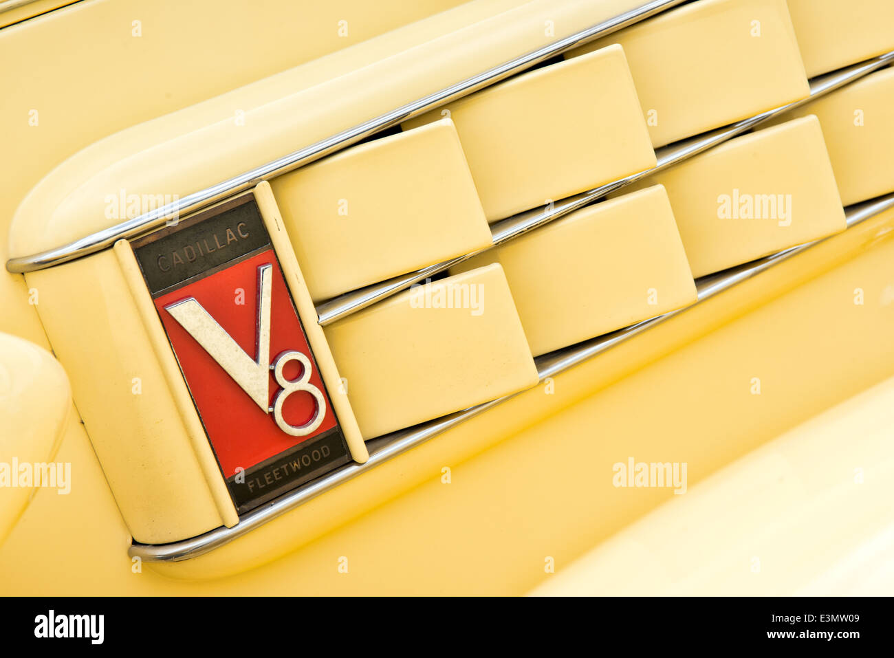 Detail of  the badge & vent on a yellow 1936 Cadilac Fleetwood V8 - Stock Image