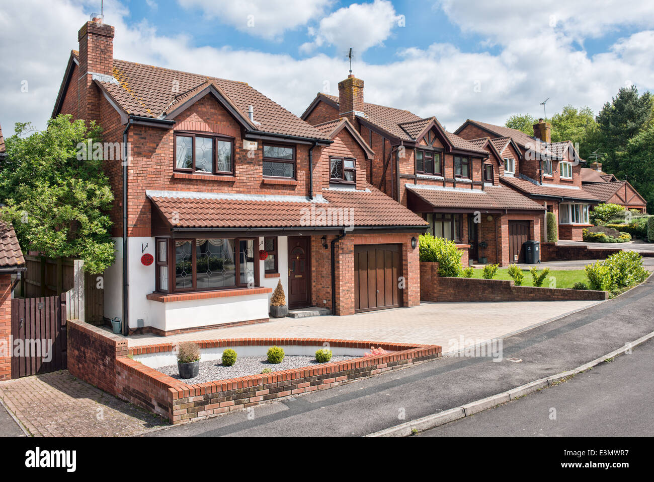 A typical row of suburban detached homes on a sunny street in Swindon, Wiltshire, UK - Stock Image