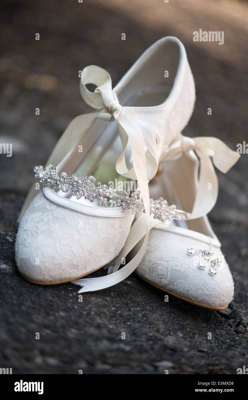 A pair of brides antique white, ribbon tied wedding shoes posed together with the bridal jewelry - Stock Image