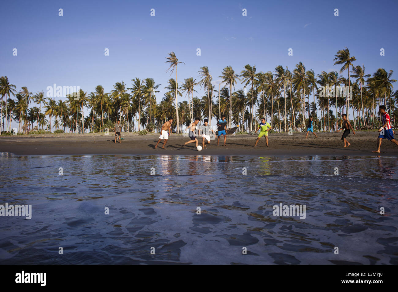 Banda Aceh, Aceh, Indonesia. 25th June, 2014. Teenagers playing football at a beach in Banda Aceh, Aceh, Indonesia.Football Stock Photo