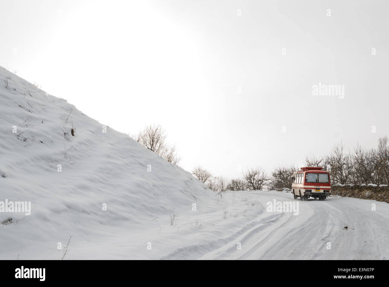 Small bus driving on a slippery winter road, Armenia - Stock Image