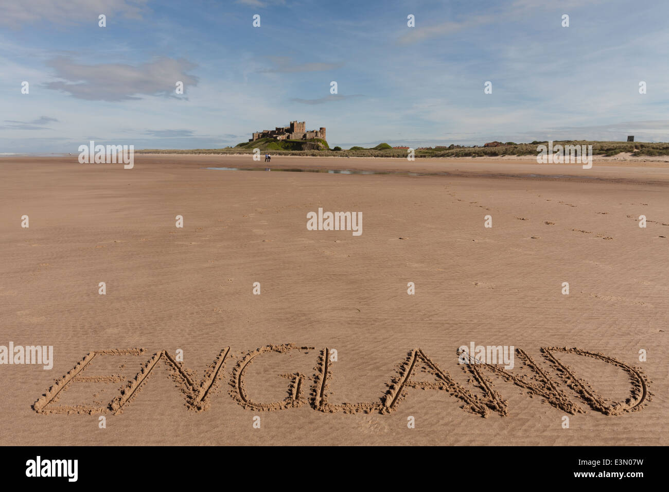 England written in sand on beach at Bamburgh, UK with Bamburgh Castle in background - Stock Image